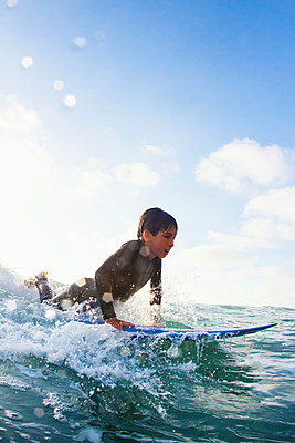 Young boy practicing on surfboard - p429m884149 by Yew! Images