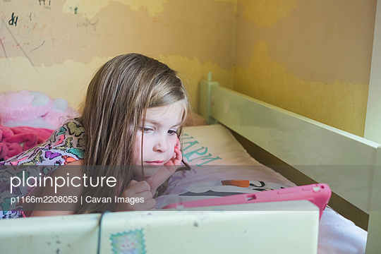 Young girl lying on her bed looking at her device - p1166m2208053 by Cavan Images