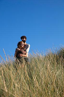 Junges Paar den in Dünen - p1212m1168690 von harry + lidy