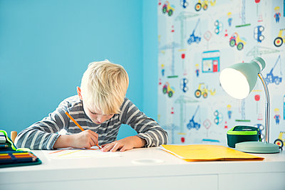 Focused boy doing homework at desk in children's room - p300m2083769 by Michelle Fraikin