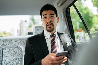 Young businessman with cell phone in a taxi talking to the driver - p300m2140619 by Juri Pozzi