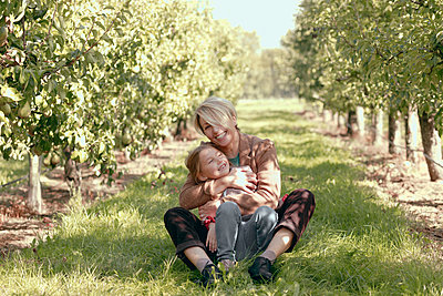 Smiling mother and daughter relaxing at orchard - p300m2275633 by Katharina Mikhrin