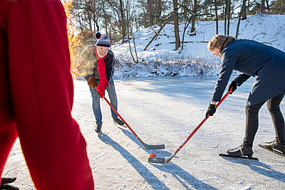 Senior man playing ice hockey with friends on snow during winter - p300m2281813 by Frank van Delft