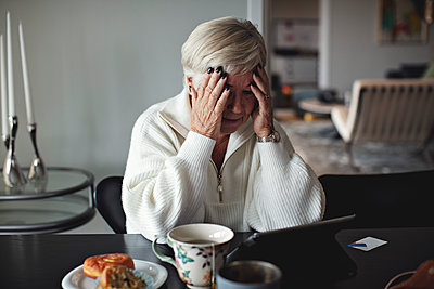 Worried senior woman with head in hands looking at digital tablet while sitting by dining table at home - p426m2213456 by Maskot