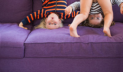 Portrait of young boy and girl doing headstand on sofa - p429m1014662 by JLPH