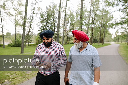 Mature Indian men wearing turbans in park with smartphone - p1192m2129848 by Hero Images