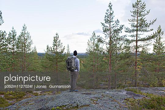 Sweden, Vasterbotten, Umea, Man standing on rocks looking at view - p352m1127024f by Jonas Gunnarsson