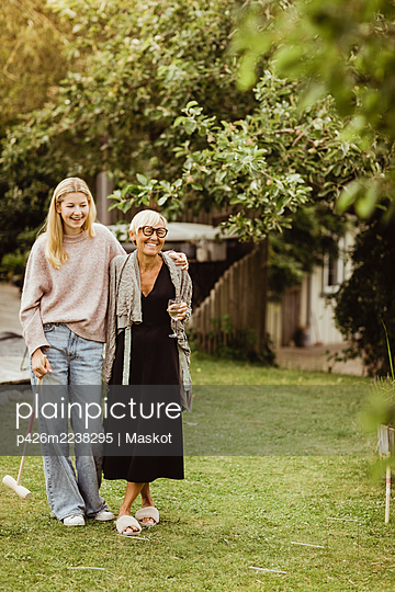 Grandmother and granddaughter spending leisure time in front yard - p426m2238295 by Maskot