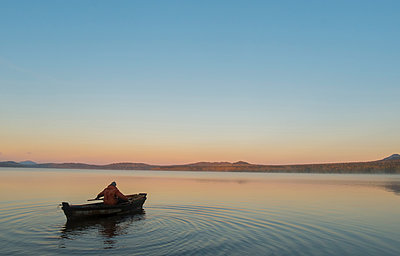 High angle view of man in boat on lake against clear sky during sunset - p1166m1182980 by Cavan Images