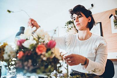 Confident florist arranging flowers at store - p1166m1474274 by Cavan Images