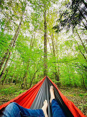 POV of feet in hammock in a forest surrounded by trees while camping - p1166m2190482 by Cavan Images