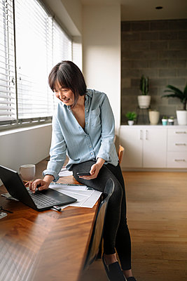 Businesswoman using laptop and smart phone in office - p1192m2124208 by Hero Images
