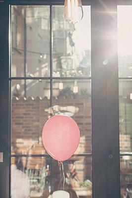 Pink balloon against lattice window at sunlight - p1598m2164169 by zweiff Florian Bier