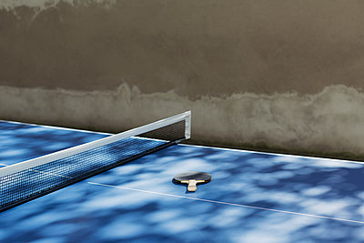 High angle view of table tennis bat by net on table - p301m1196881 by Norman Posselt