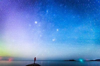 Sweden, Medelpad, Juniskar, Silhouette of man looking at night sky - p352m1126395f by David Schreiner