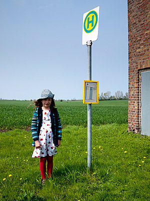 Girl waiting at bus stop - p3883166 by Weather