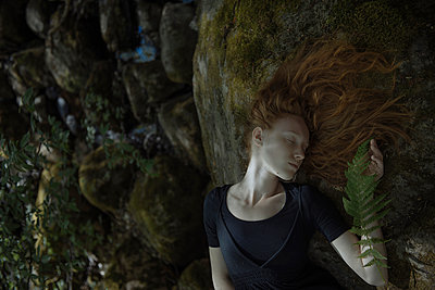 Caucasian woman with red hair laying on rock - p555m1531639 by Ivan Ozerov