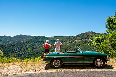 Tourists with cabriolet taking a break - p813m1159507 by B.Jaubert