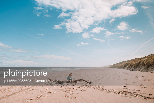 Toddler sits on driftwood on beach - p1166m2088698 by Cavan Images