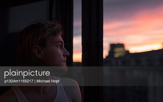 Junger Mann betrachtet einen Sonnenuntergang - p1324m1165217 von michaelhopf