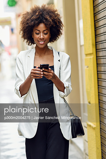 Portrait of smiling young woman with curly hair looking at cell phone - p300m2004275 von Javier Sánchez Mingorance