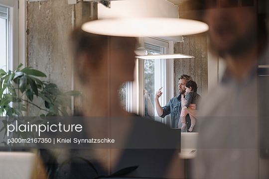 Casual businessman carrying little daughter at the window in office - p300m2167350 von Kniel Synnatzschke