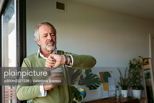 Man with coffee cup checking time while standing by window at home - p300m2227238 by Valentina Barreto
