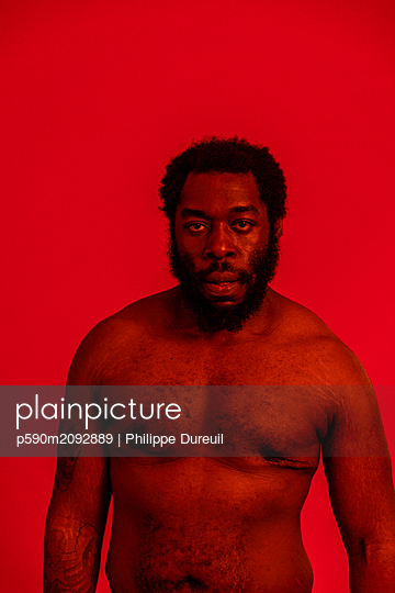 Black man with a red filter looking at the camera with anger - p590m2092889 by Philippe Dureuil