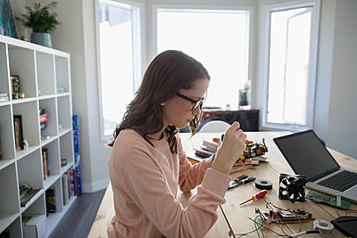 Teenage girl assembling laptop electronics at table - p1192m1490775 by Hero Images