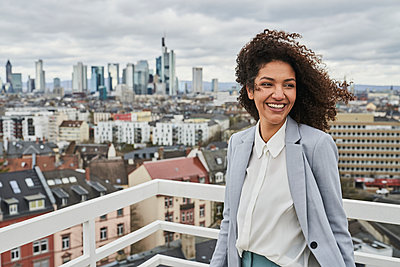 Smiling female entrepreneur on rooftop in city - p300m2281420 by Annika List