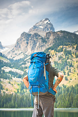A backpacker stops at a lake to look at the mountains. - p343m1184701 by Rob Hammer