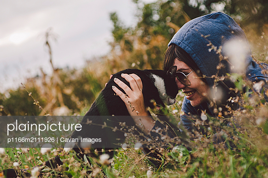 Happy woman playing with cat while sitting amidst plants at park - p1166m2111926 by Cavan Images