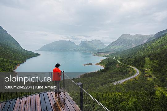 Norway, Senja island, rear view of man standing on an observation deck at the coast - p300m2042284 von Kike Arnaiz