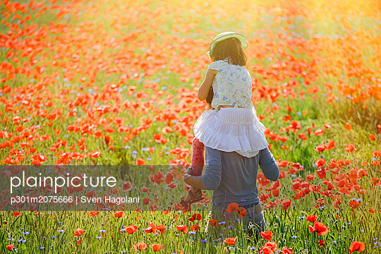 Father carrying daughter on shoulders in sunny, idyllic rural field with red poppy flowers - p301m2075666 by Sven Hagolani