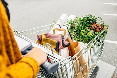 Midsection of woman pushing trolley full of purchases in car park - p1264m1089029f by Astrakan