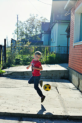 Boy playing football - p1412m2030778 by Svetlana Shemeleva