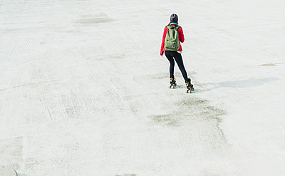 Young woman with backpack inline skating on parking level - p300m1101201f by Uwe Umstätter