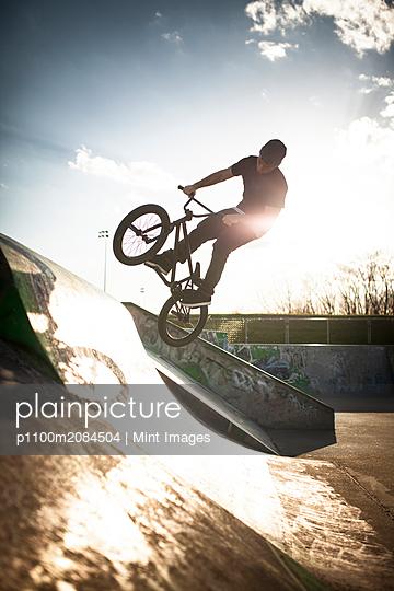 Caucasian man riding BMX bicycle at skate park,Boucherville, Quebec, Canada - p1100m2084504 by Mint Images