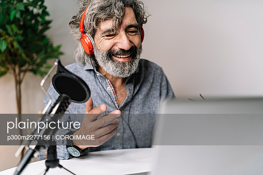 Smiling senior male podcasting while wearing headphones at office - p300m2277156 by COROIMAGE