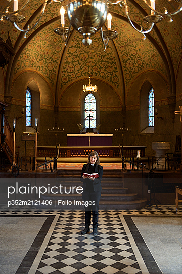 Priest reading bible in church - p352m2121406 by Folio Images