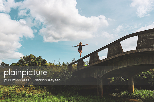 Philippines, Woman balances over a bridge - p986m2227411 by Friedrich Kayser