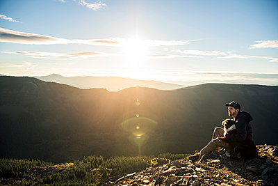 Man sitting with dog on cliff against mountain range - p1166m1142884 by Cavan Images