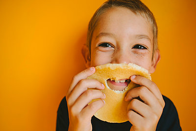 Happy boy looking away while holding bread with hole against orange wall at home - p1166m1474453 by Cavan Images
