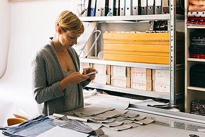 Fashion designer using cell phone in studio - p300m2029799 by Visualspectrum