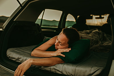 Tired woman sleeping in car trunk at dusk - p300m2220632 by David Molina Grande