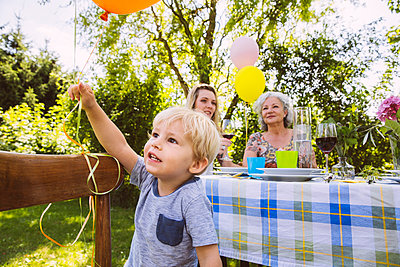 Boy at table with family of three generations in garden - p300m981080f by Mareen Fischinger