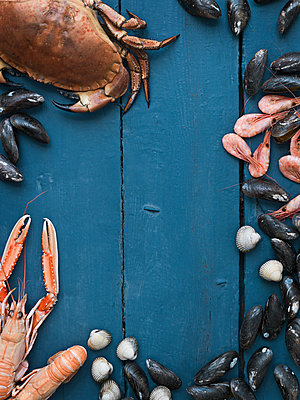 Seafood against blue wooden background - p312m1075994f by Matilda Lindeblad
