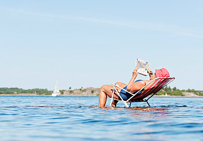 View of man lying on chair standing in lake - p312m1551859 by Johner Images