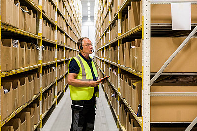 Side view of senior male worker with digital tablet looking at packages on rack while talking through headset at distrib - p426m2018832 by Maskot