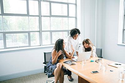 Businesswomen using laptop in meeting - p555m1504111 by John Fedele